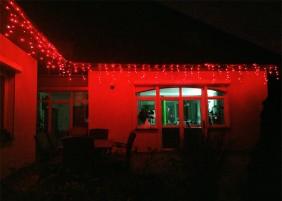 Zwisające diody LED tworzą ozdobne sople. Kurtyna zewnętrzna w kolorze czerwonym z timerem i efektem błysku.