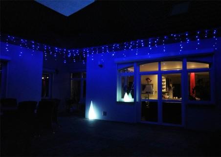 Zwisające diody LED tworzą ozdobne sople. Kurtyna zewnętrzna w kolorze niebieskim z timerem i efektem błysku.